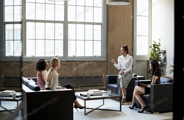 Seated female manager talking to team at an informal meeting