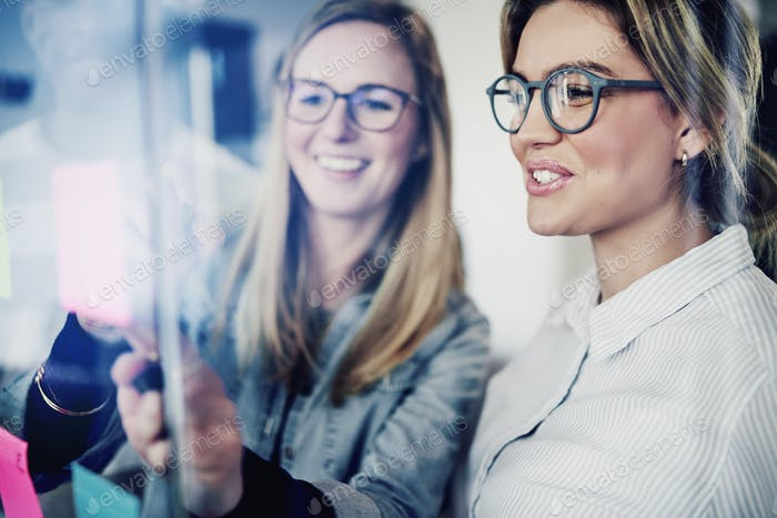 Two businesswomen brainstorming with sticky notes on a glass wall