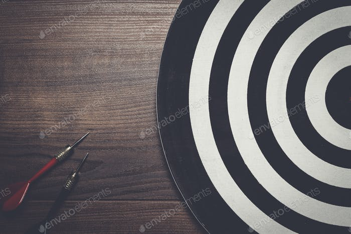two darts and target on wooden background