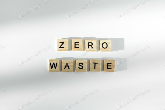 Zero waste text written by wooden letters on white background. Flat lay, top view.