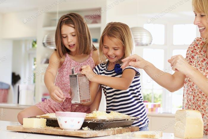Mädchen mit Mutter machen Käse auf Toast