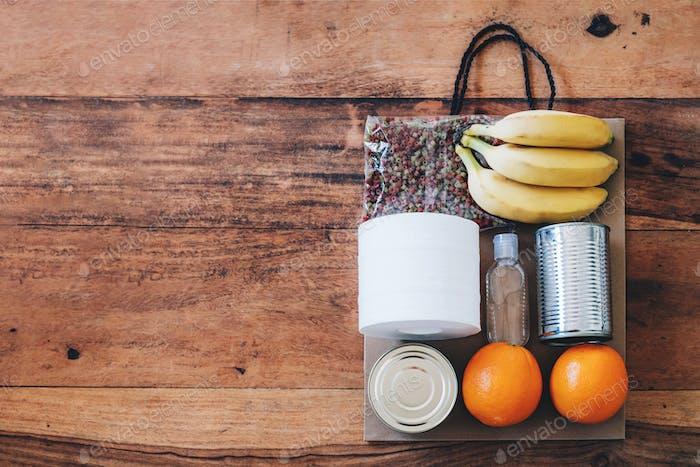 Bolsa de papel con alimentos, papel higiénico y desinfectante de manos.