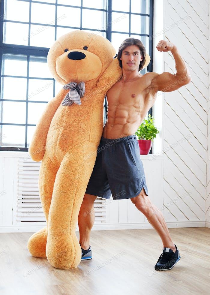 Männchen posiert mit großem roten Teddybär.