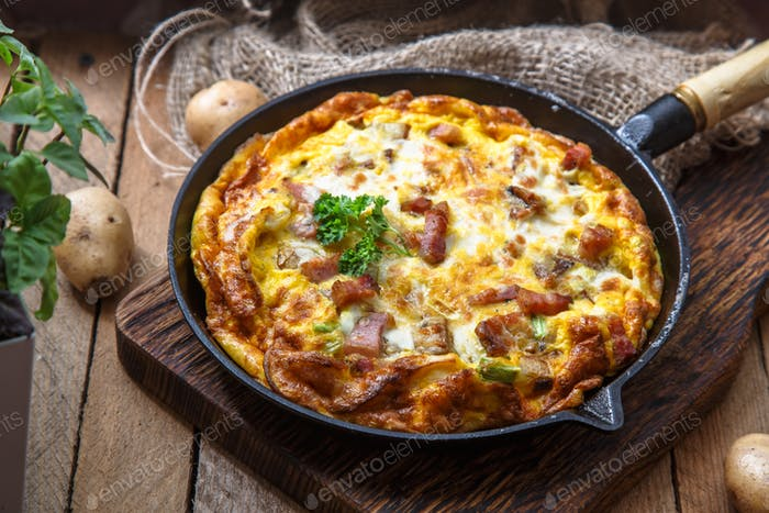 French omelette Savoyarde with bacon, cheese and leeks in fry pan, rustic