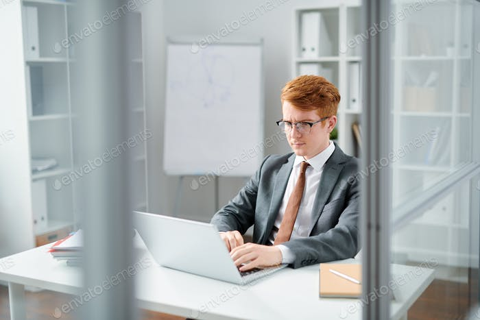 Young lawyer in elegant suit reading online data