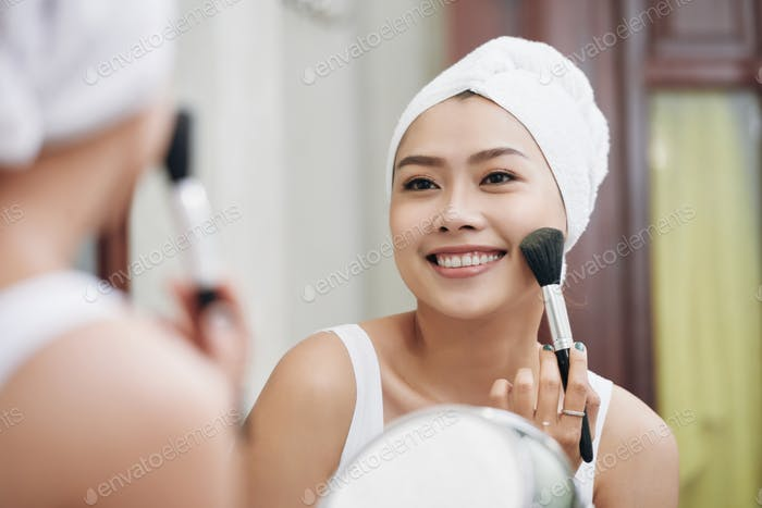 Smiling woman applying makeup in bathroom mirror