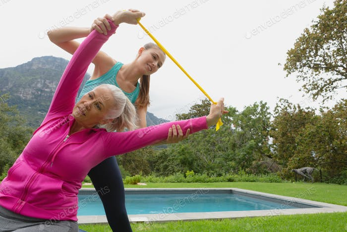 Caucasian female trainer assisting active senior woman to exercise with resistance band