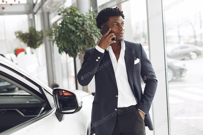 Schöner und eleganter schwarzer Mann in einem Autosalon
