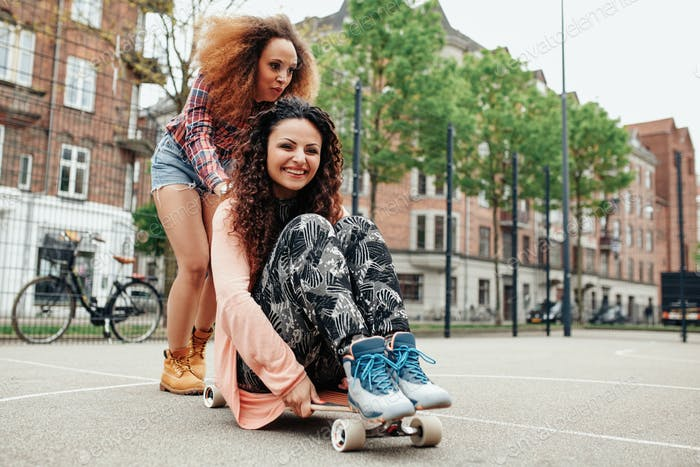 Happy young girls playing with longboard