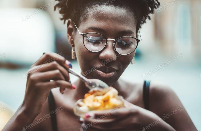 Chica africana comiendo un postre
