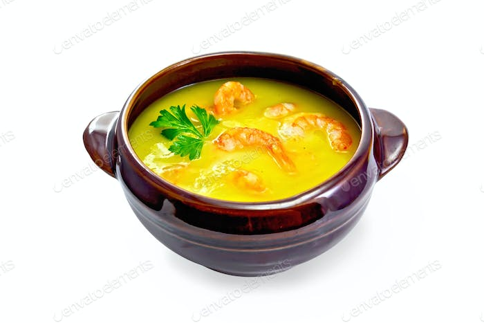 Soup-puree pumpkin with shrimps in clay bowl