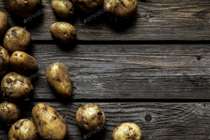 fresh organic potatoes varieties over plank rustic background