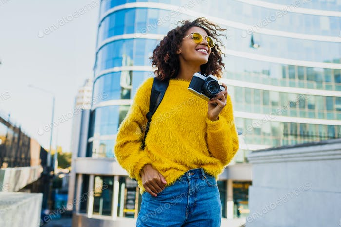Happy confident  african woman holding photo camera