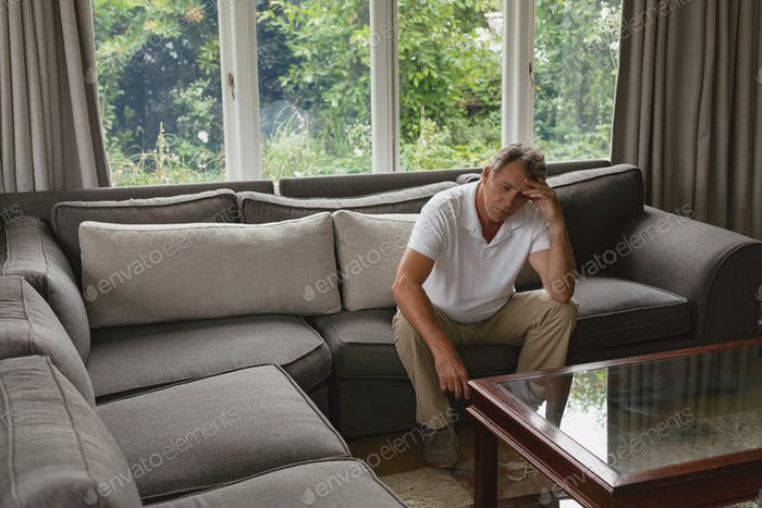 Tensed active senior Caucasian man with hand on forehead sitting on sofa in a comfortable home
