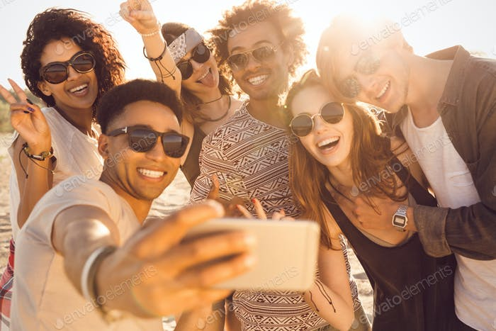 Group of multiracial happy friends taking selfie and having fun