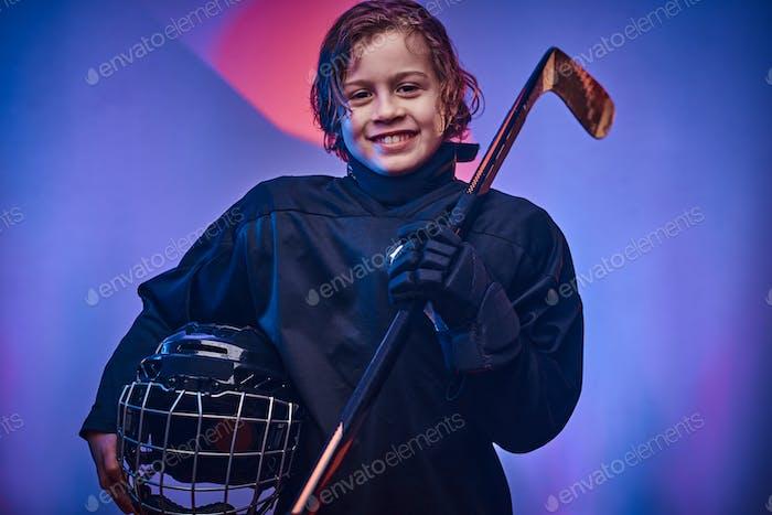 Junge Hockeyspieler posiert in Uniform für ein Fotoshooting in einem Studio