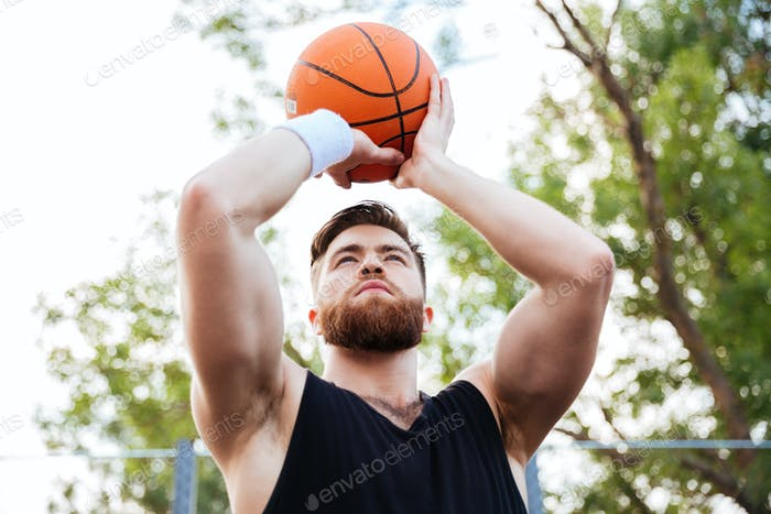 Portrait of a handsome man in sports wear playing basketball