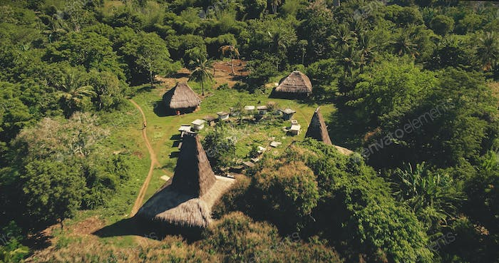 Traditional houses of Indonesia village at tropical green landscape aerial view. Unique buildings