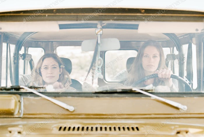 Two women on a road trip in the desert, driving in a 4x4.