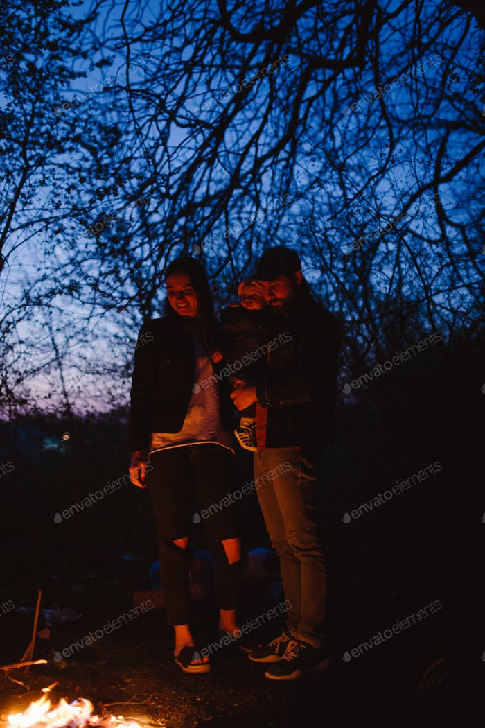 Happy family mother father and their little son stand in front of a fire and looking at the fire at