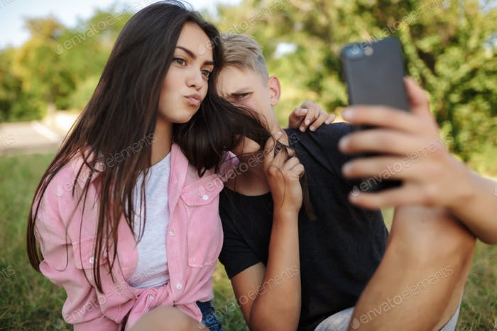 Cute couple sitting on lawn and embracing each other while making funny selfie in park