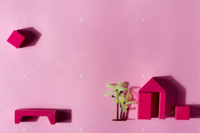 Handmade house from wooden blocks with palm and shadows