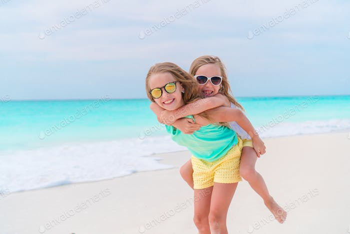 Adorable little kids play together on the beach