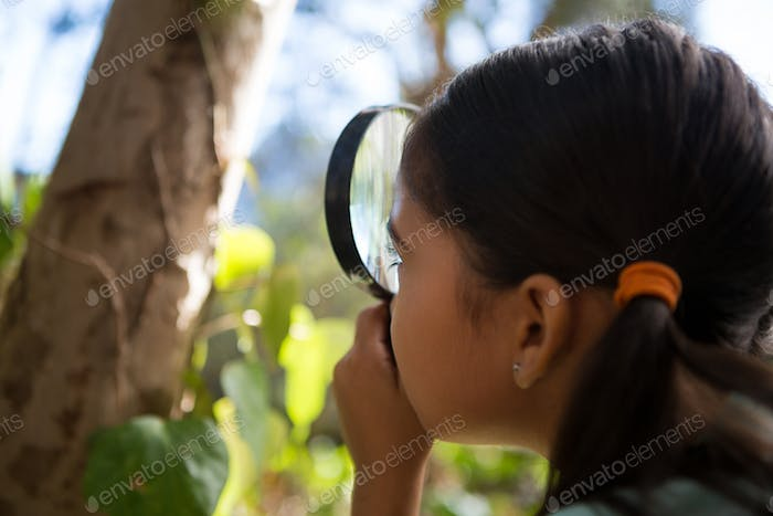 Little girl holding magnifying glass exploring nature