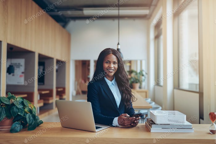 Smiling African American businesswoman working alone in an office lounge