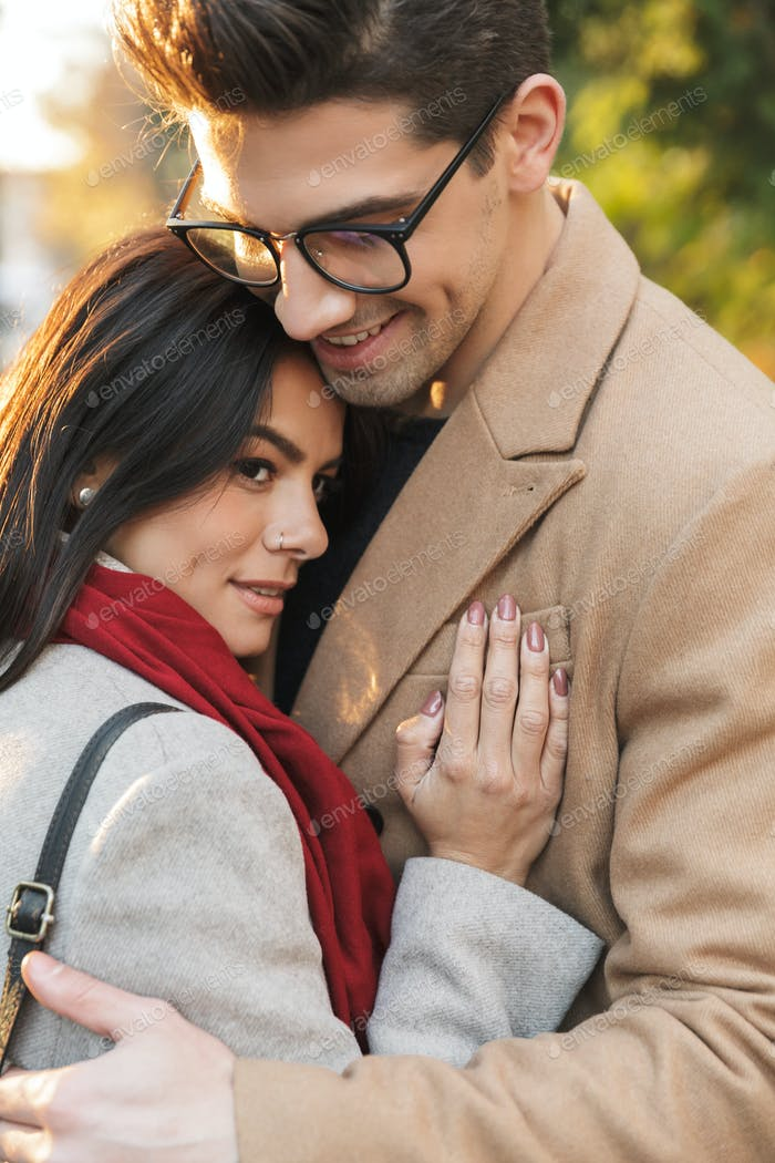 Portrait of casual romantic couple smiling and hugging each other while walking in autumn park