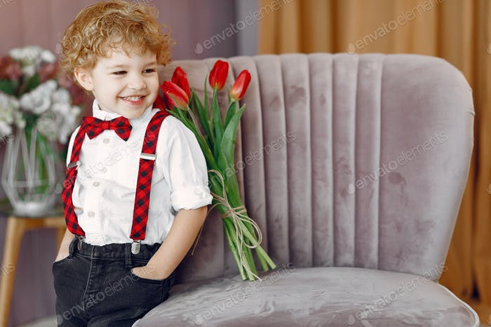 Elegant little boy in a studio with bouquet of tulip