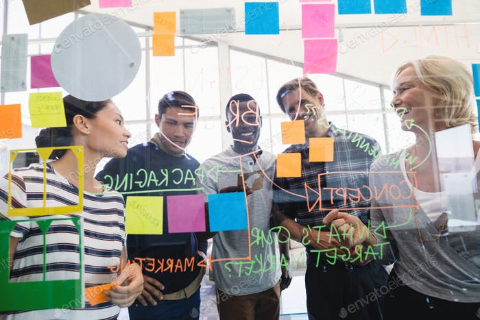 Business people seen through glass wall with plan