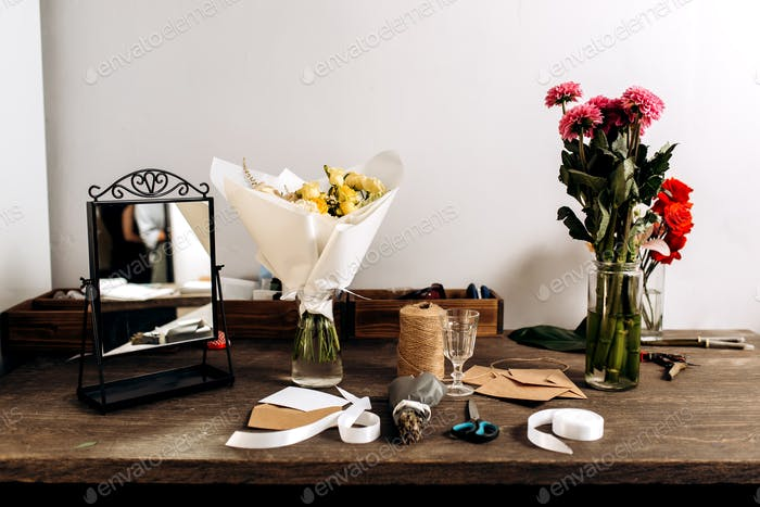 There are three different bouquets, mirror, postcard, envelopes, bobbin of twine, scissors and white