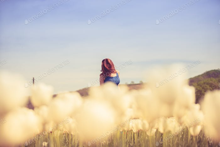 Gorgeous woman in tulips field in sunny day