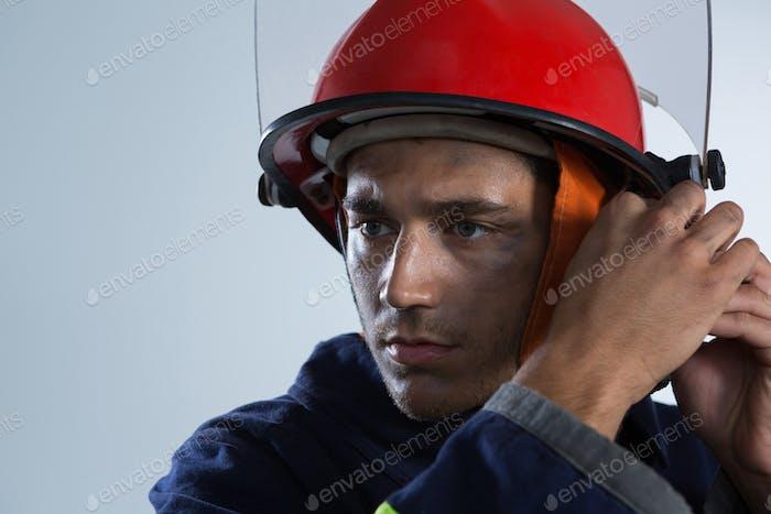 Feuerwehrmann Einstellung seines Sicherheitshelms