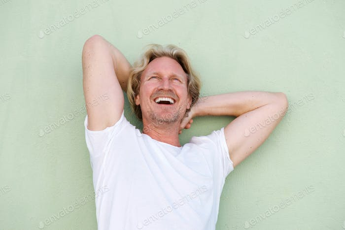 middle aged guy laughing with hands behind head