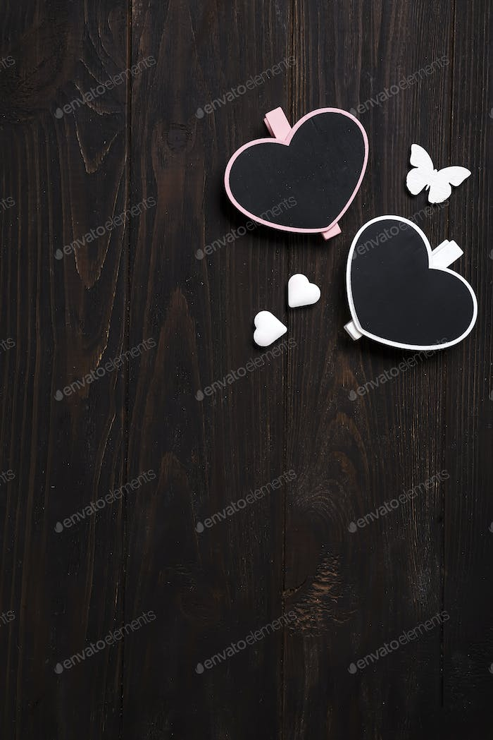 two wooden hearts with butterfly on wooden background.
