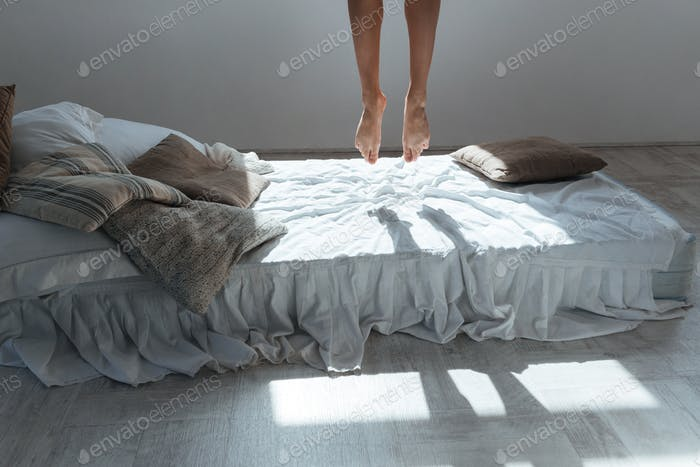 Slim legs of young woman flying in air above bed