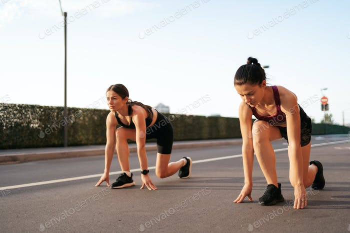 Female runners ready to start running and racing each other