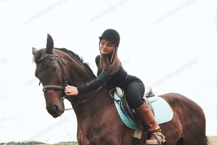 Young pretty girl - riding a horse, equestrian sport in spring time