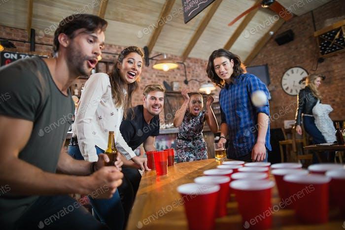 Jóvenes Amigos disfrutando de la cerveza pong Juego en Restaurante