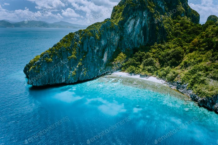 Aerial drone view of tropical Entalula Island. Huge steep rocks cliffs mountains surrounding blue