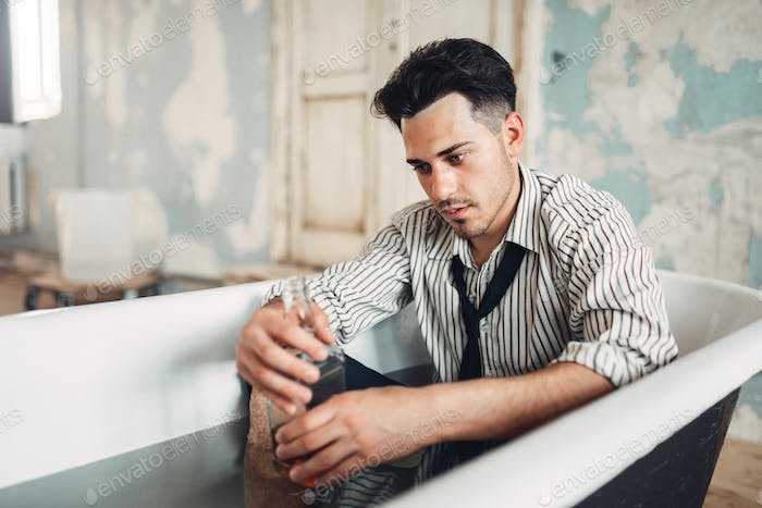 Drunk businessman in bathtub, suicide man concept