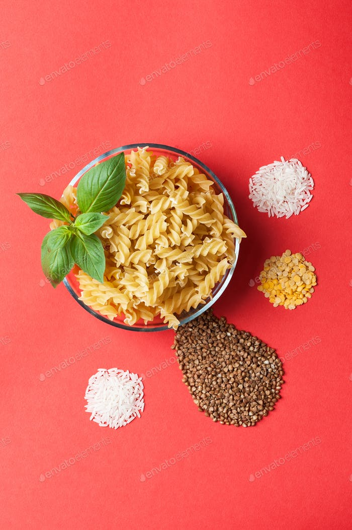 Pasta, rice, buckwheat and lentils on a red background.
