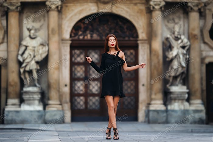 Stylish young girl in a black dress in urban style on the street of the city of BRNO. Czech