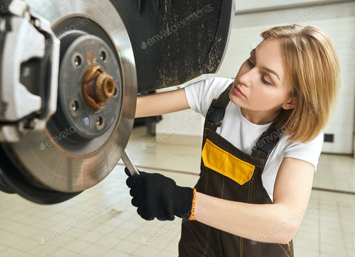 Focused female mechanic changing tire of auto in workshop