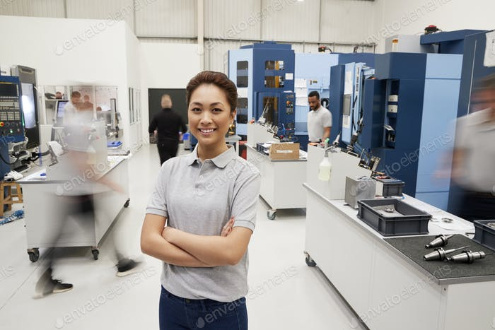 Portrait Of Female Engineer On Factory Floor Of Busy Workshop