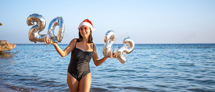 A young woman in a swimsuit and a santa claus hat holds Christmas ballons on the seashore.