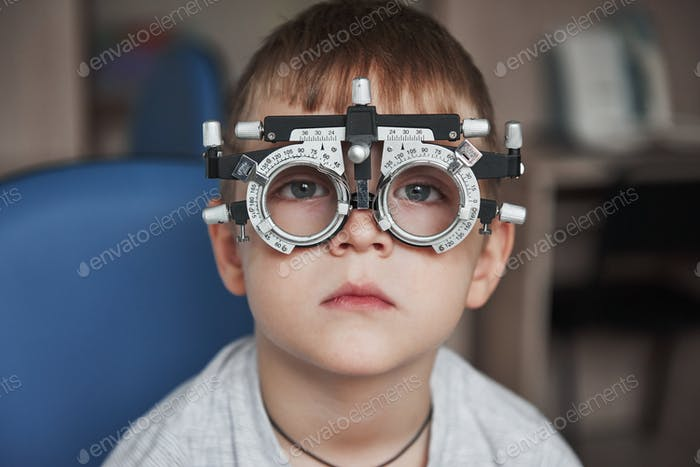 Watching straight into the camera. Close up portrait of child in special glasses