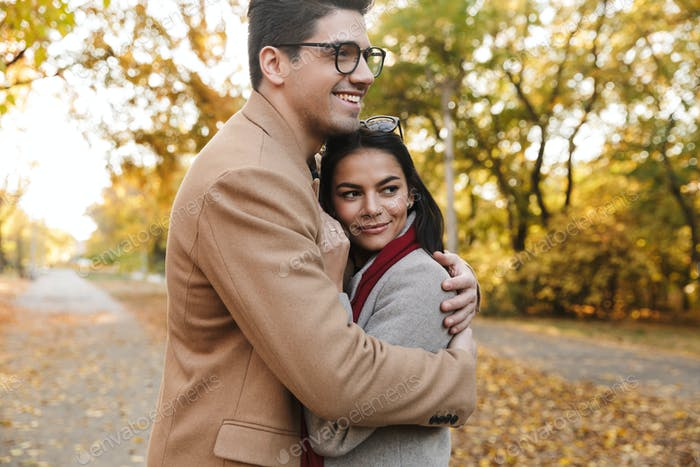 Image of young brunette couple smiling and hugging in autumn park